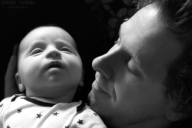 High tonal contrast photos are primarily light and dark or white and black elements with a sharp difference between them like this dramatic image | Photography Tips | Father and baby in black and white.