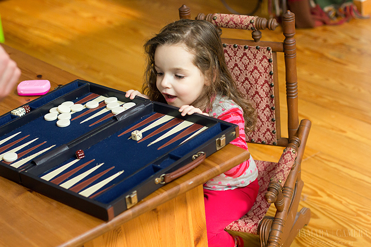 Little girl playing backgammon | Natural Light Photography