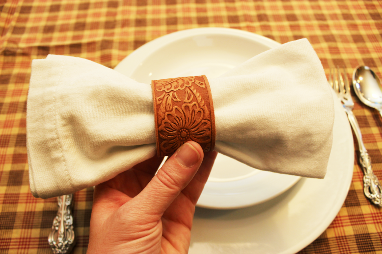 Cloth napkin bow with a DIY leather napkin ring. Simple to make, beautiful addition to your next tablescape.