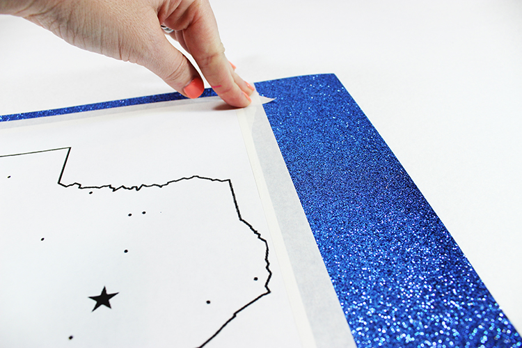 Tape your silhouette template onto your glittery scrapbook paper.