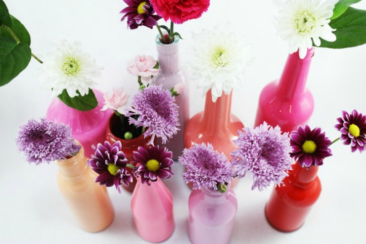 Painted glass bottle vases are a great DIY to brighten up any room with a pop of color.