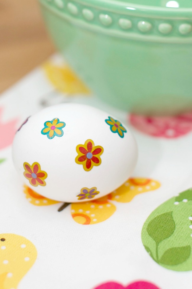 Adding stickers to your hard boiled eggs is the first step in this fun and unique Easter egg dying technique.