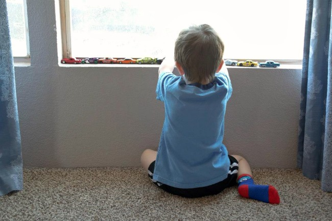 Little boy playing with cars on the window sill.