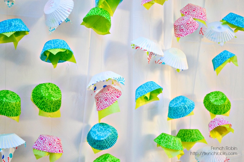 Use fishing line, cupcake liners, and tissue paper to create a fun DIY photo backdrop for your next party.