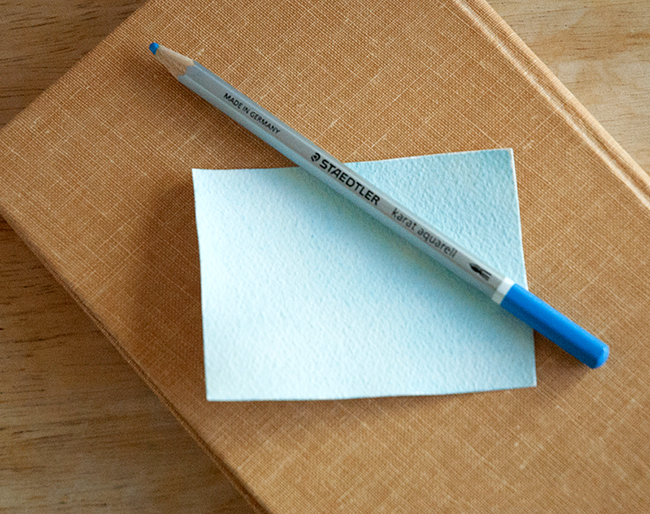 Lightly color a pice of watercolor paper for the background for your book page art.