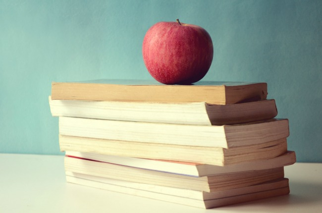 Apple sitting on a stack of books.