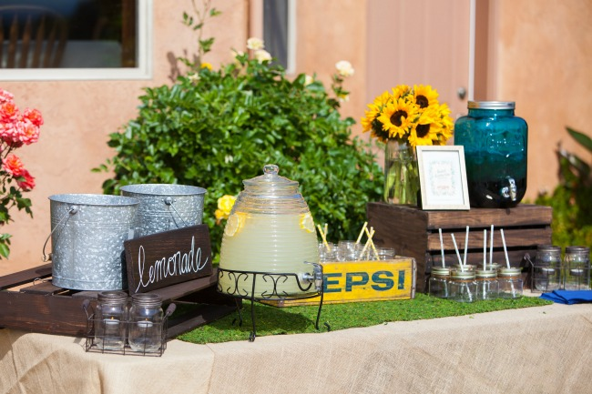 A dedicated table for drinks is a must for an outdoor summer party! I love how the old Pepsi crate looks with the sunflowers and the moss runner. Super cute!