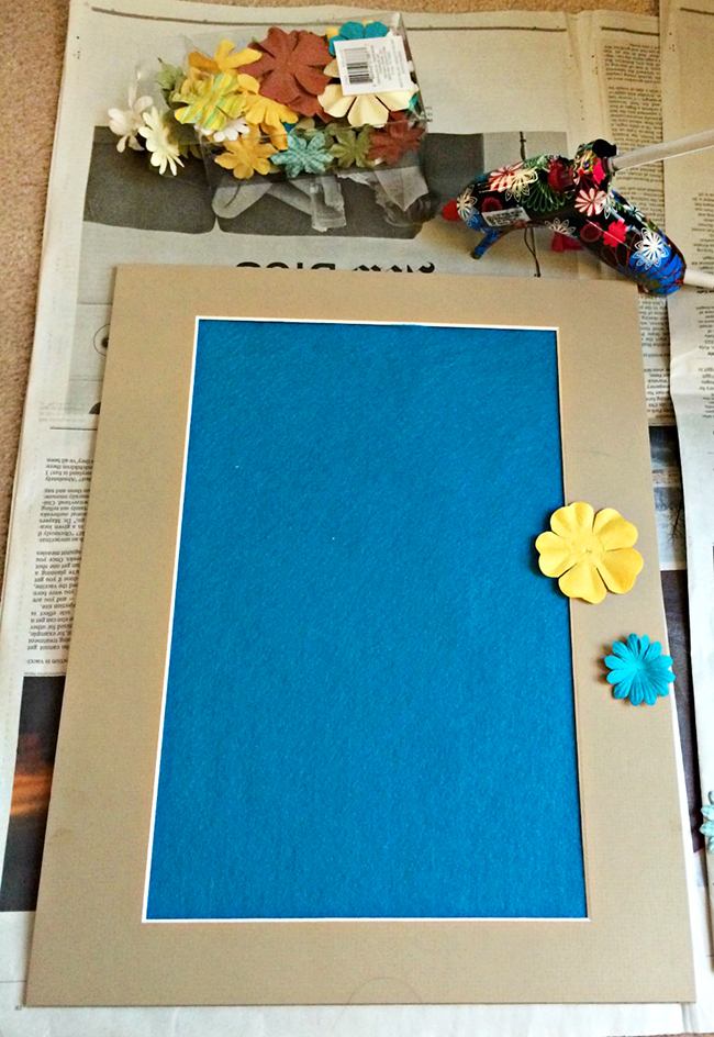 Hot glue flowers and other fun embellishments to a photo mat for a quick and easy DIY project.