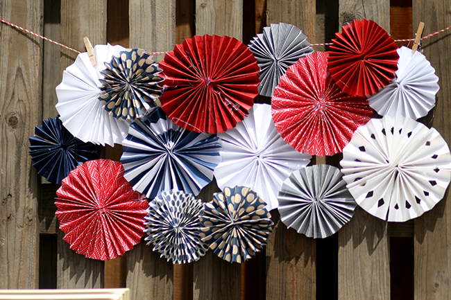 An old pallet makes a great background for an outdoor July 4th party tablescape. This paper fan project is easy to make, and it turns out SO cute.