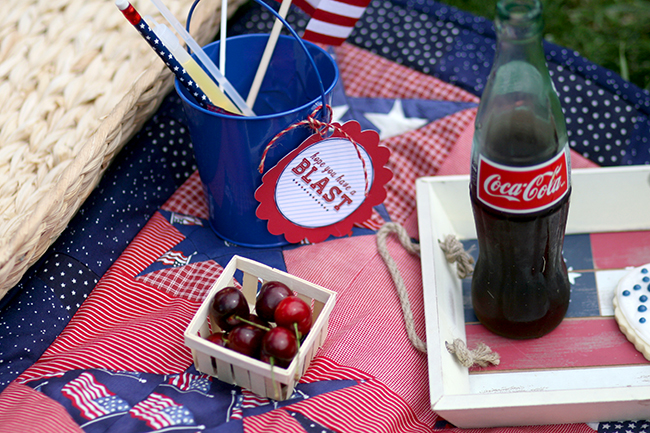 Coke in a glass bottle, cherries, and treat buckets with July 4th themed goodies. Great ideas for your next fourth of July party.