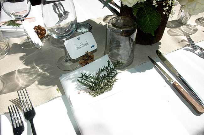 A sprig of evergreen is a nice touch for the napkins in a rustic outdoor wedding.