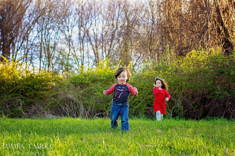 Kids running through a field on the edge of the woods.