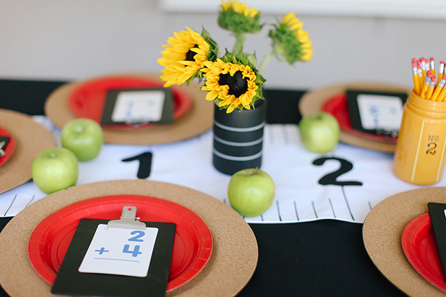A back to school party needs a school theme! Love how this table looks with the ruler table runner and an apple by every place setting.