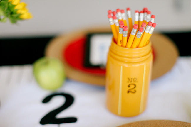 A yellow mason jar with a bouquet of pencils - perfect for a back to school party table.