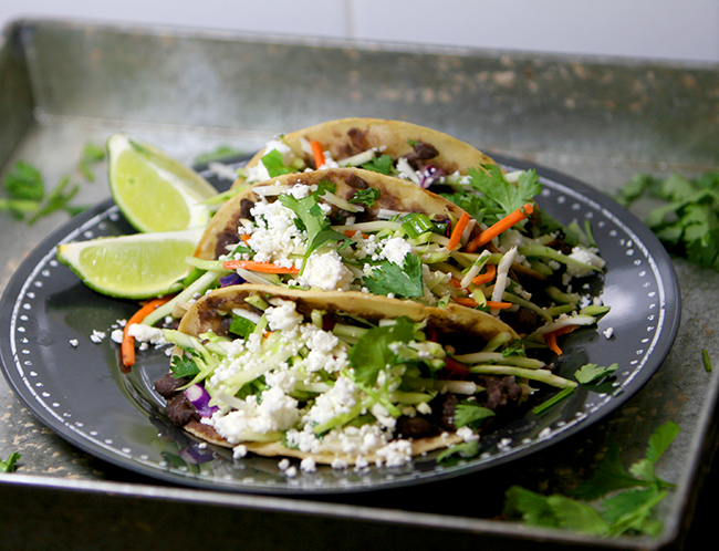 Healthy black bean tacos topped with delicious cilantro lime slaw. They will leave you begging for a second helping!