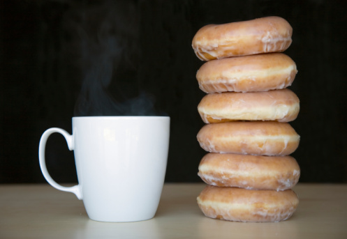 Stack of doughnuts next to coffee cup