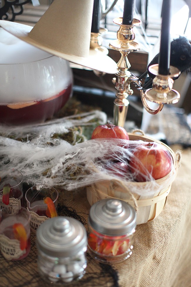 Black pillar candles, apples with cobwebs, and spooky treats are served at this Evil Queen Party!
