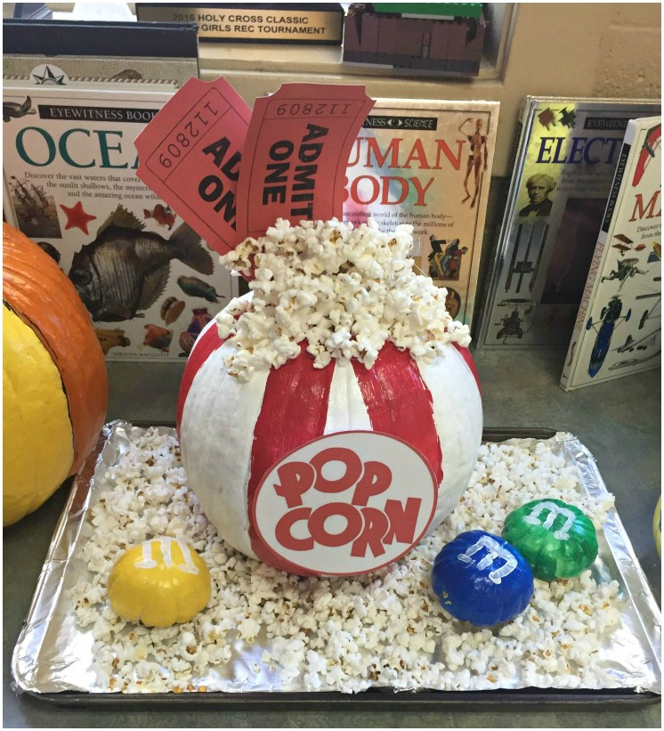 No carve pumpkin decorating - love this pumpkin painted like a bag of popcorn, complete with movie tickets and miniature pumpkins painted like M&M's.