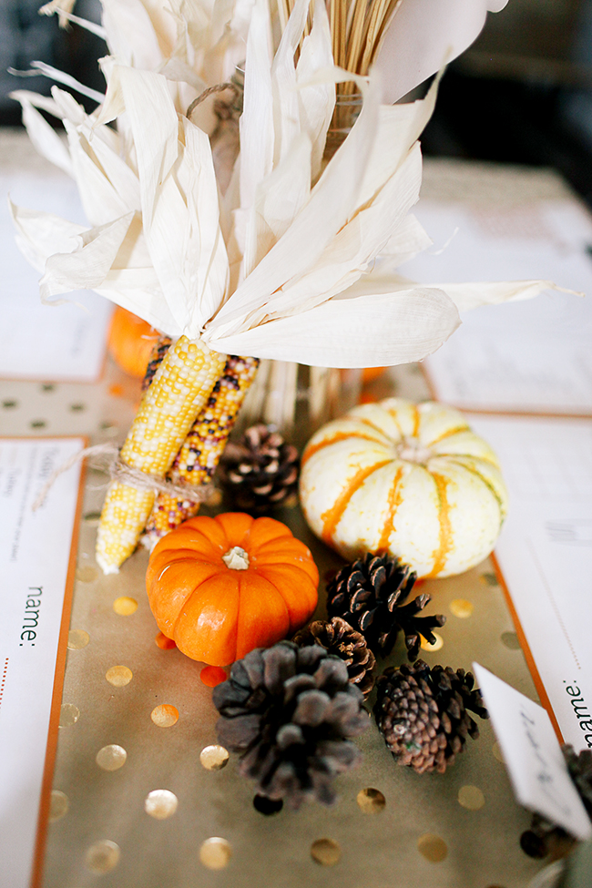 Make kids a centerpiece for their table using pumpkins, pinecones, and wheat.