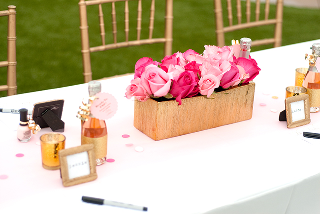 Pink roses for the centerpiece, and small frames and champagne bottles for place settings.