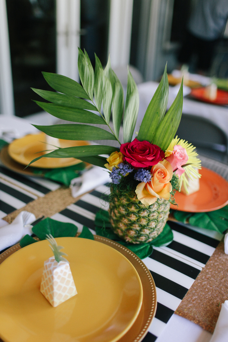 Combine bright colors and black and white place mats! The pineapple flower arrangements are the perfect final touch for tropical party decor.