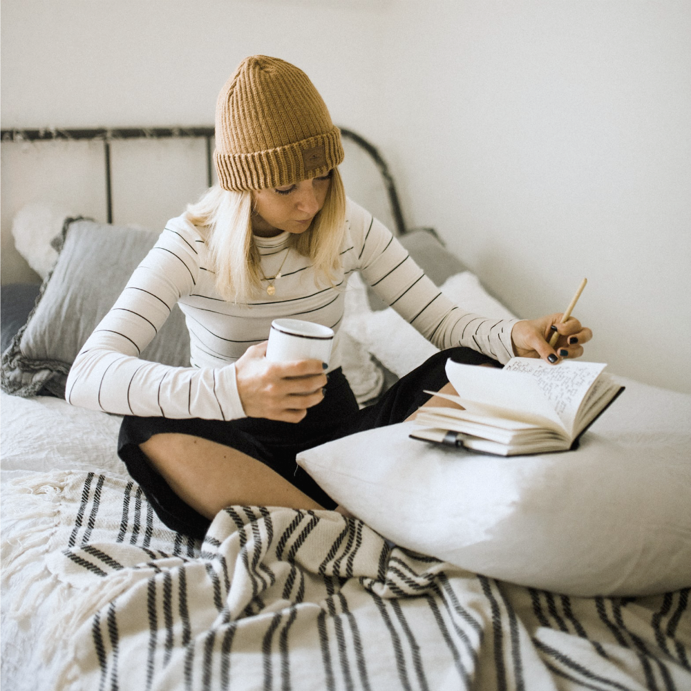 woman in bed reading and writing