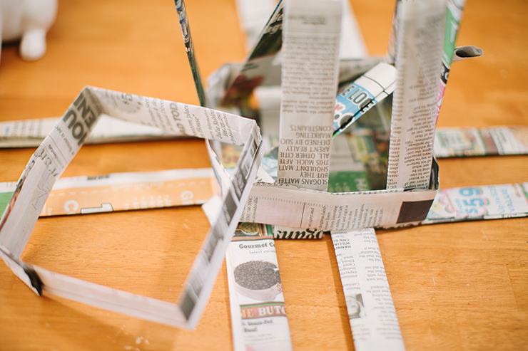 Form newspaper strips into a square to make your newspaper basket.