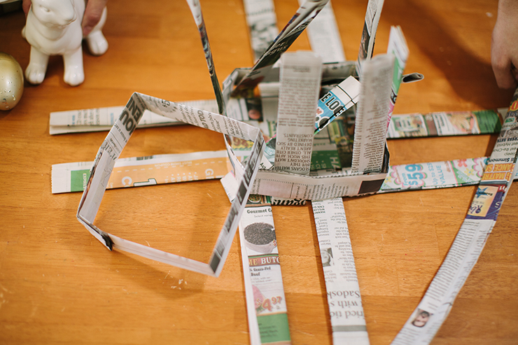 Fold the base strips up around the square to form a basket with newspaper.
