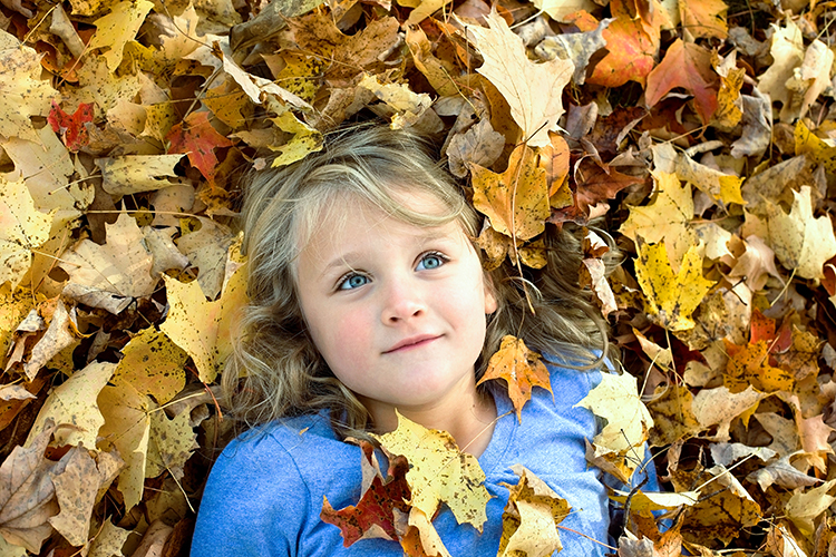 capture the world you see - girl laying in pile of leaves