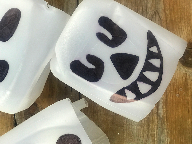 Draw spooky faces on milk jugs for a great Halloween DIY!