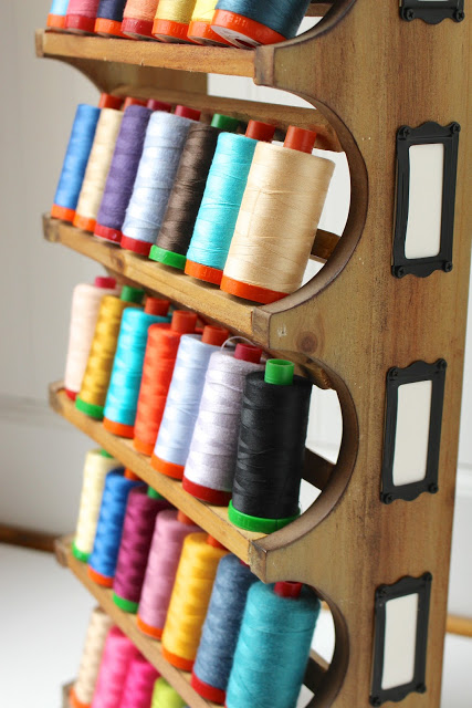 Turn a wine rack into a thread holder.