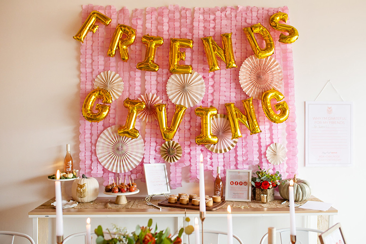 Friendsgiving buffet table with balloon friendsgiving sign