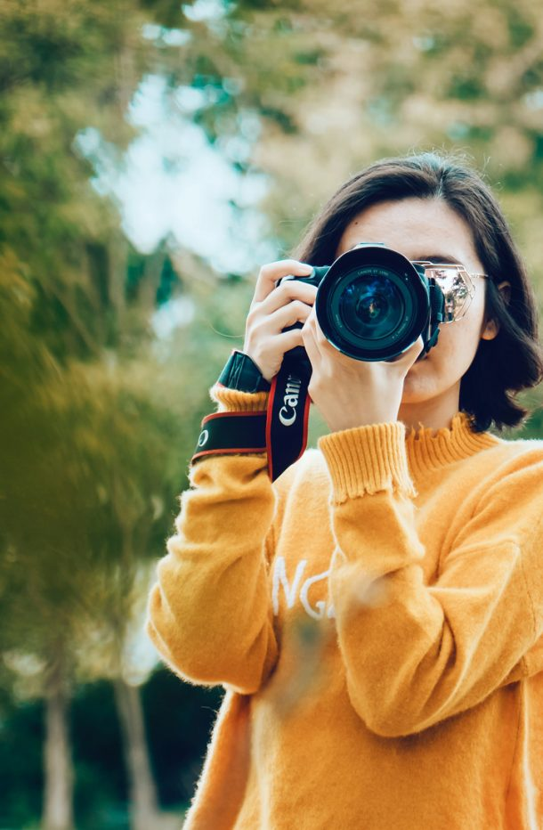 Woman holding DSLR camera taking a photograph