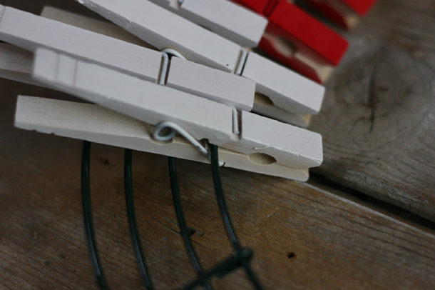 Closeup of white clothespins on wire wreath frame