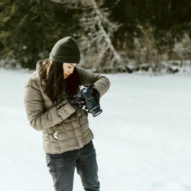 woman taking pictures in the snow