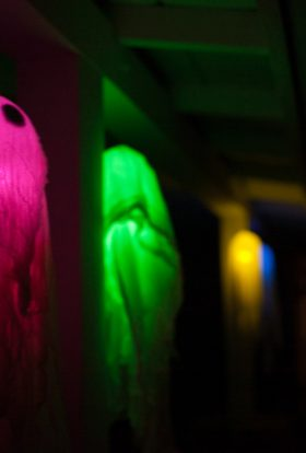 Floating ghosts glowing in different colors hanging on a porch in the dark.