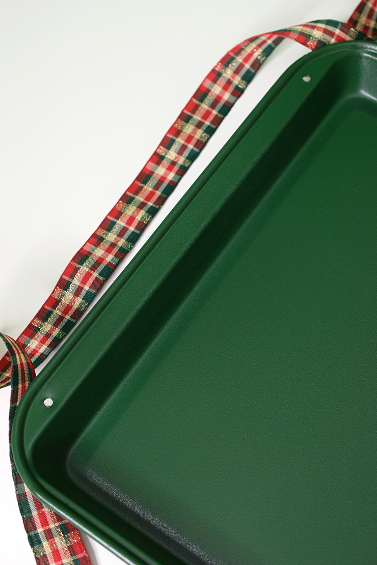 metal cookie sheet with two holes drilled in the side, painted green