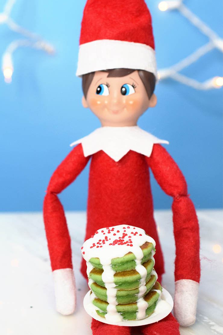 elf on the shelf holding a green mini pancake breakfast with icing and sprinkles