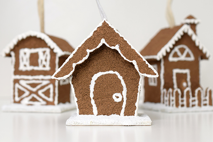 three birdhouses painted with sand to create a gingerbread look