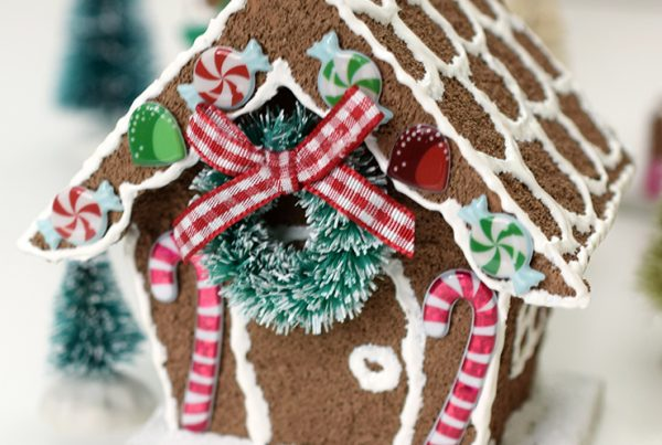 birdhouse, painted like a gingerbread house, with Christmas decorations and stickers to finish the look