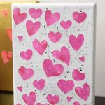 Pink hearts on white canvas with black flecks of paint.