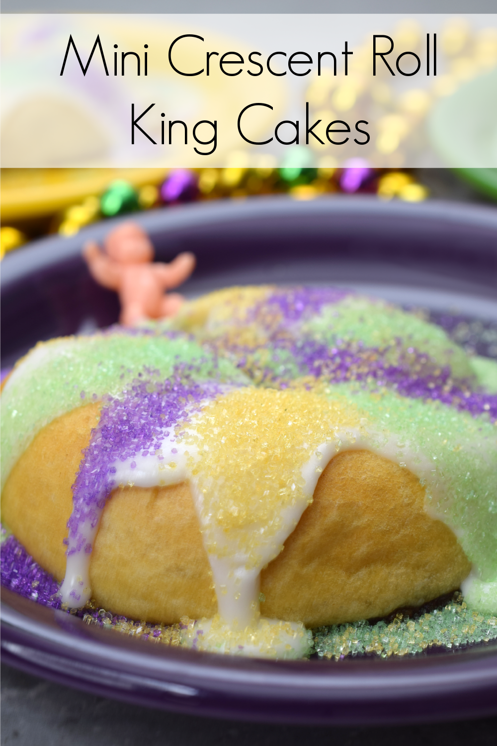 Mini crescent roll king cakes on purple plate with mardi gras beads and plastic baby in the background.