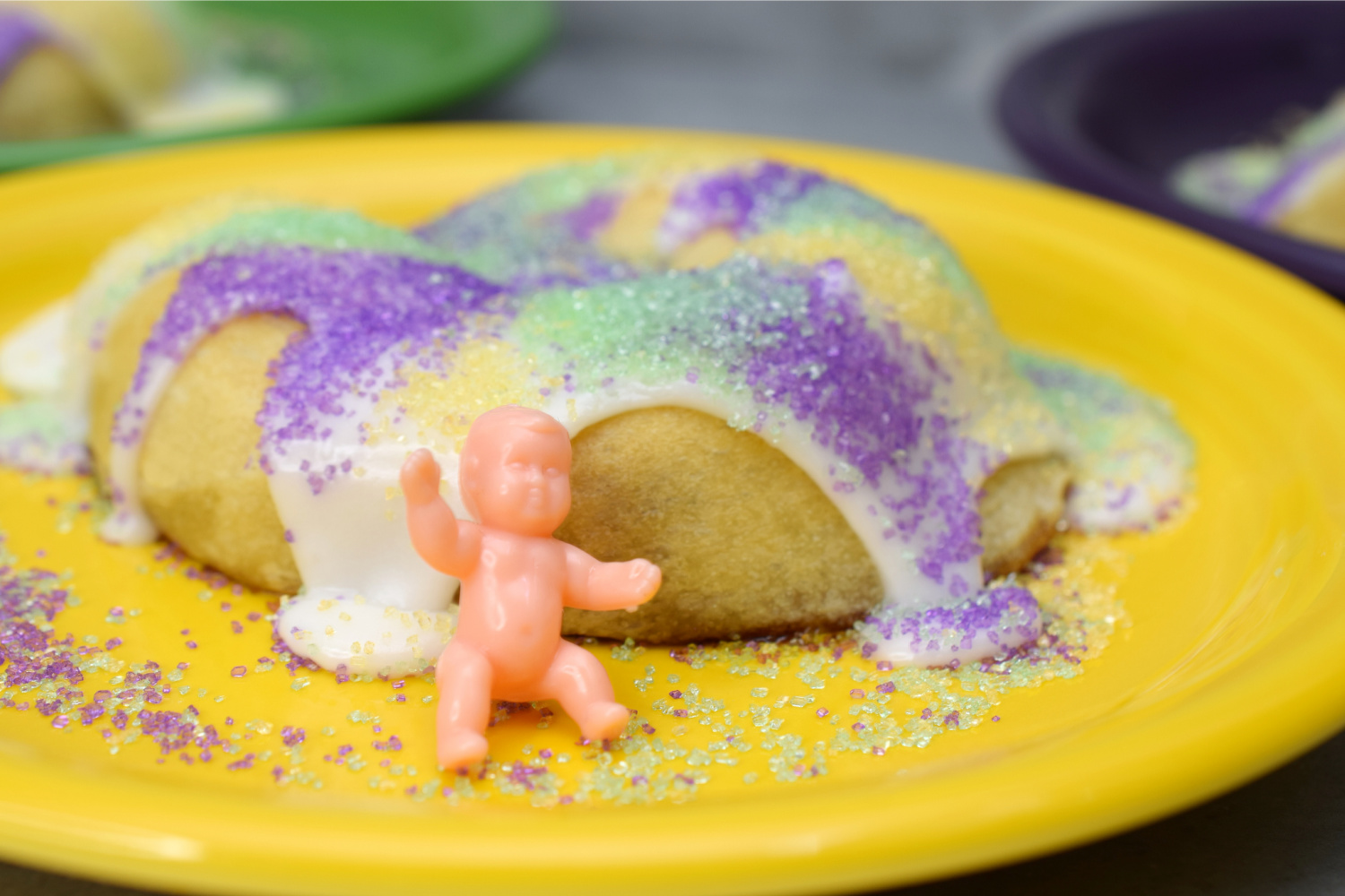 King Cake on a yellow plate with a plastic baby.