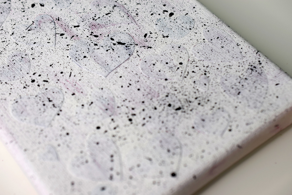 Canvas with flicks of black paint on white paint.