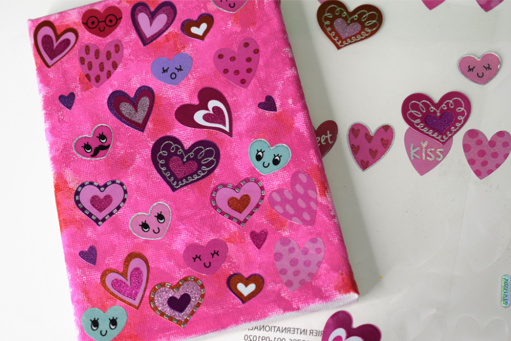 heart stickers on top of painted canvas.