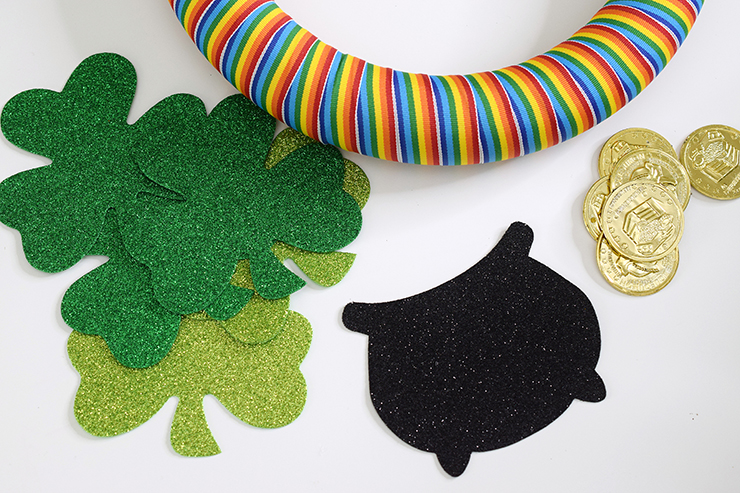 Supplies for St. Patrick's Day rainbow wreath, including rainbow ribbon, black pot and green shamrocks decals and gold coins.