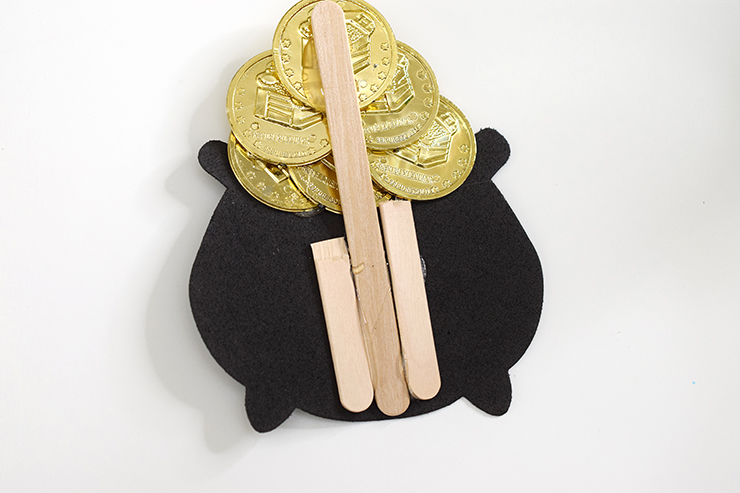 Attach gold coins and black cauldron to a popsicle stick to hot glue to the wreath.
