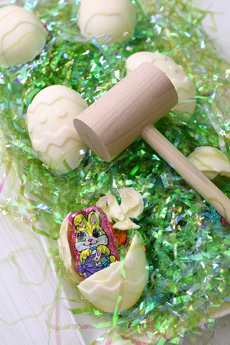 Broken chocolate piñata Easter Egg setting on platter next to wooden mallet and unbroken eggs on green Easter grass.