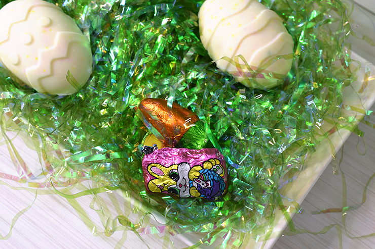Easter candy placed on platter with green Easter grass and covered with white chocolate Easter egg halves.