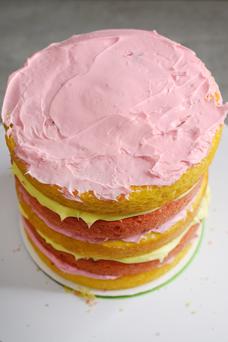 Layered cake with lemonade and strawberry cake layers alternating and pink and yellow icing alternating.